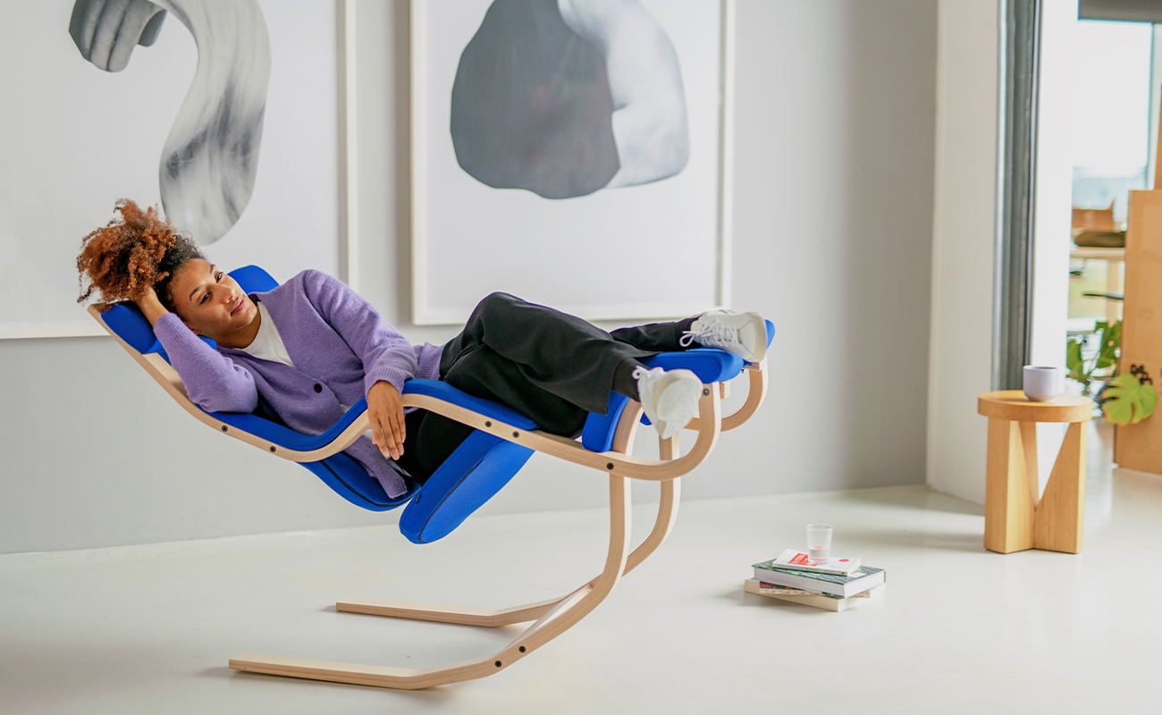 Woman relaxing in Gravity chair in modern workspace