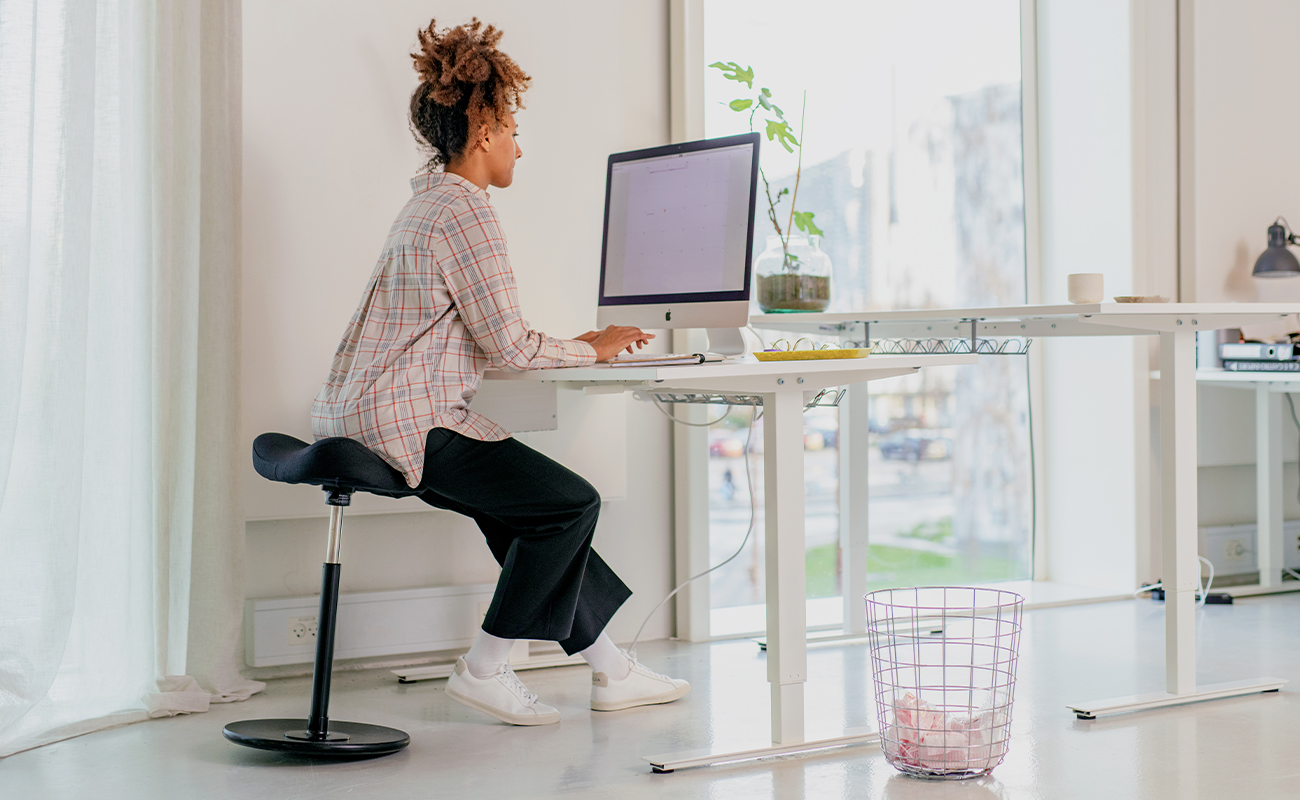 Woman sitting on Move in modern office space. Sit stand chair stool, design by Per Øie.