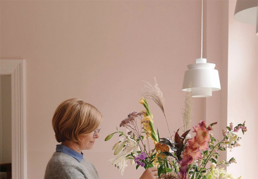 woman arranging flowers in a room with pink walls